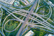 canvas print picture - Aerial view of road interchange or highway intersection with busy urban traffic speeding on the road. Junction network of transportation taken by drone.