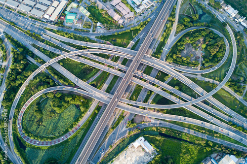 Türaufkleber Natur Aerial view of road interchange or highway intersection with busy urban traffic speeding on the road. Junction network of transportation taken by drone.