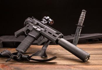 Studio shot of a semi-automatic rifle with a silencer and a Ka-Bar.