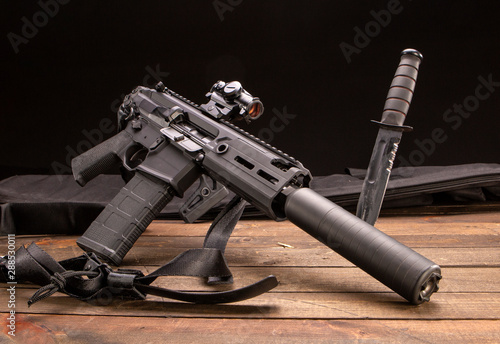 Cuadros en Lienzo  Studio shot of a semi-automatic rifle with a silencer and a Ka-Bar