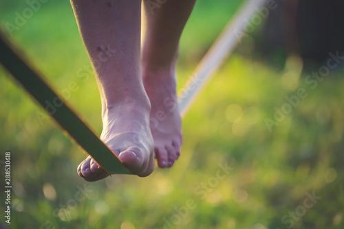 Fotografía Close up on feet walking on tightrope or slackline outdoor in a city park in sun