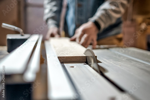 Obraz Caucasian man making wooden parts for custom furniture on machine tool called thickness planer in carpentry. Producing lumber concept - fototapety do salonu