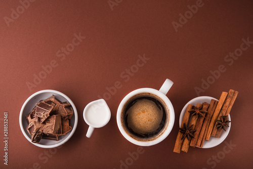 Coffee cup with milk carafe, chocolate pieces