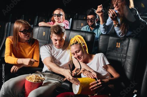 Fotografija  blonde guy splitting popcorn to his girlfriend's knees while watchin film