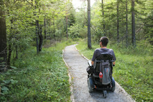 Happy Man On Wheelchair In Nature. Exploring Forest Wilderness On An Accessible Dirt Path.