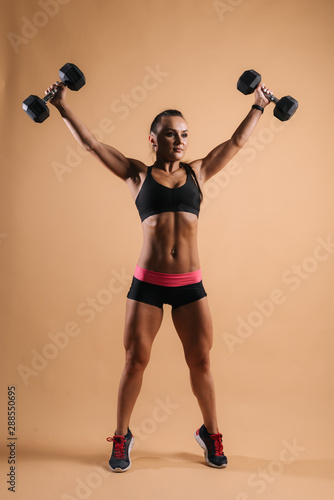 Fitness young woman with perfect muscular body in black sportswear is lifting two dumbbells overhead during weight training workout, on light red isolated background