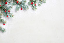 White Christmas Background With Christmas Tree Branches And Red Berries