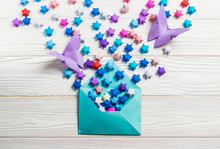 Colorful Paper Origami Lucky Paper Stars And Butterflies In Blue Envelope On White Wooden Background. Greetings Card