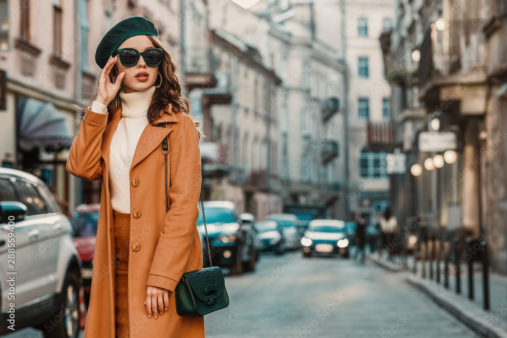 Fototapeta Outdoor autumn portrait of young elegant fashionable woman wearing trendy sunglasses, camel color coat, turtleneck, with textured leather shoulder bag, walking in street of European city. Copy space