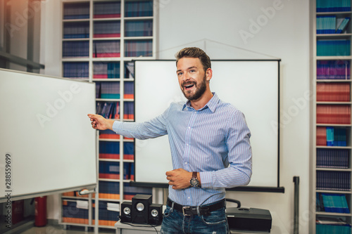 Fototapeta Smiling male coach giving presentation for audience in lecture hall obraz