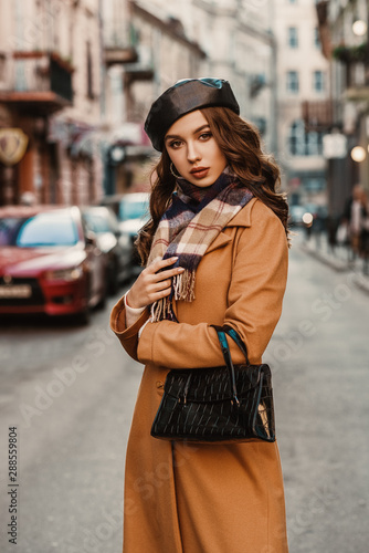 Obraz Outdoor autumn portrait of young elegant fashionable lady wearing trendy beret, camel color coat, plaid scarf, holding textured reptile faux leather baguette handbag, posing in street of European city - fototapety do salonu