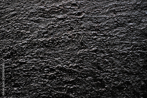 Valokuvatapetti Tar black dimpled black surface in side light, old dungeon wall.