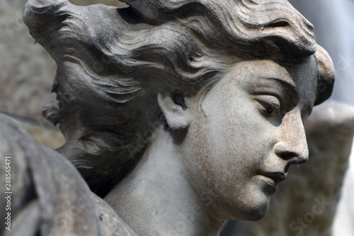 Partial view of the face of an old sandstone sculpture of an angel.