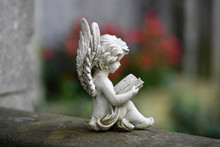 A Weathered Sculpture Of A Small, A Book Reading White Angel In Front Of A Green Background.