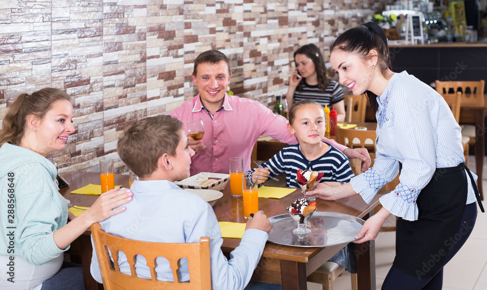 Fototapeta Polite pretty waitress serving dishes to family