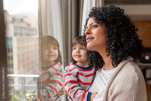 Obraz Mother and cute daughter looking through a window at home - fototapety do salonu