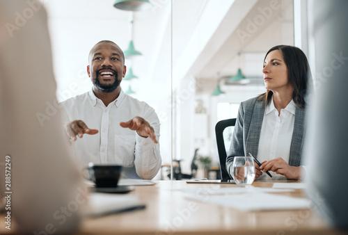 Αφίσα Smiling African American businessman talking with colleagues during a meeting
