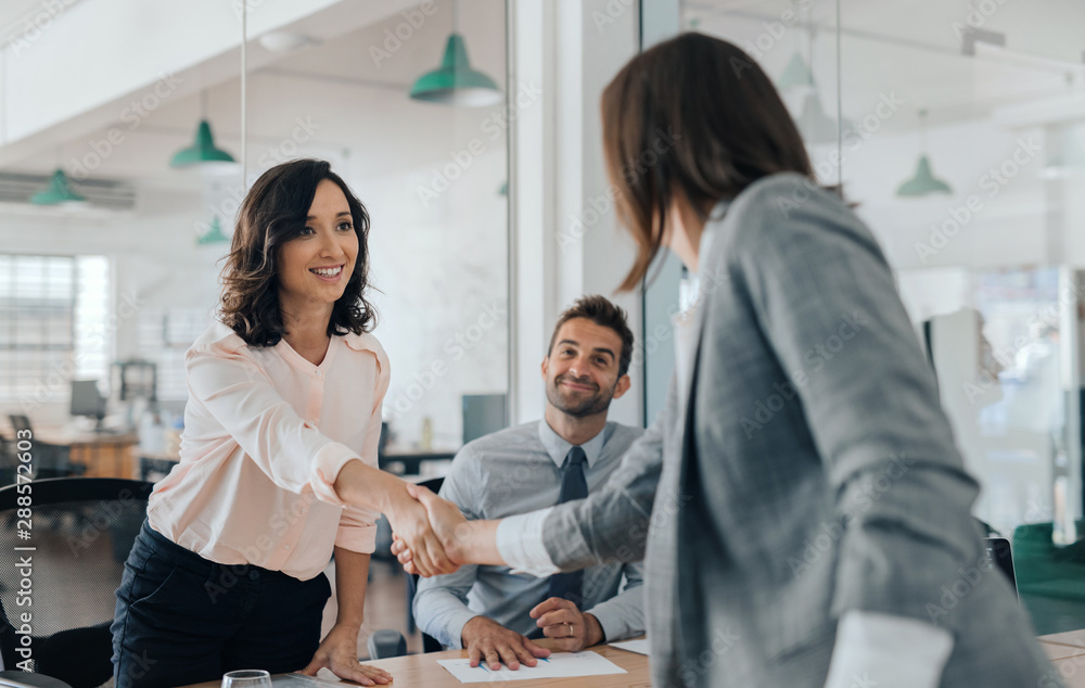 Fototapeta Smiling young businesswoman shaking hands with an office colleague