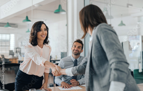 Obraz Smiling young businesswoman shaking hands with an office colleague - fototapety do salonu