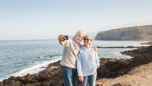 Sea Landscape Behind Two Smiling Old People. Senior Couple With Grey Hair Standing Embraced On The Cliff Looking At Mobile Phone For A Selfie. Positive Retirement