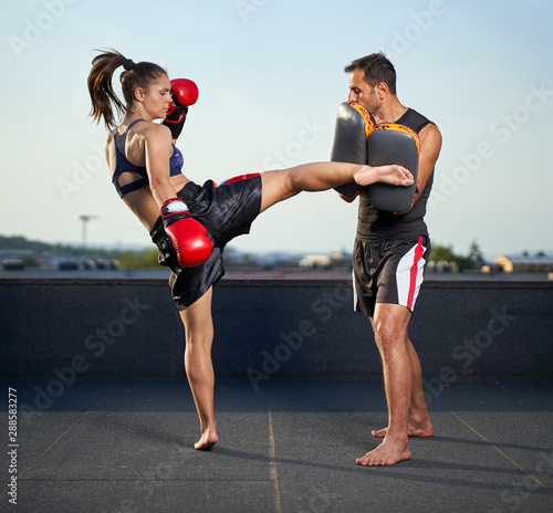 Young woman kickboxer in urban environment, training Fototapete
