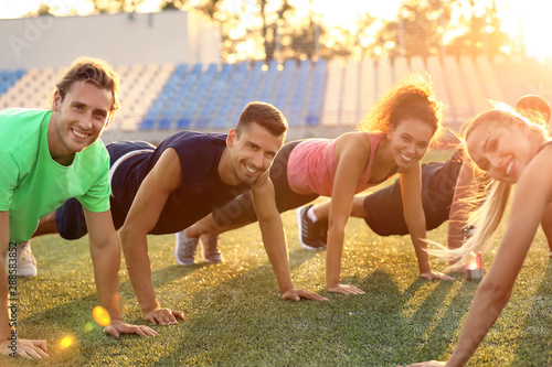 Fotografie, Tablou  Group of sporty young people training at the stadium