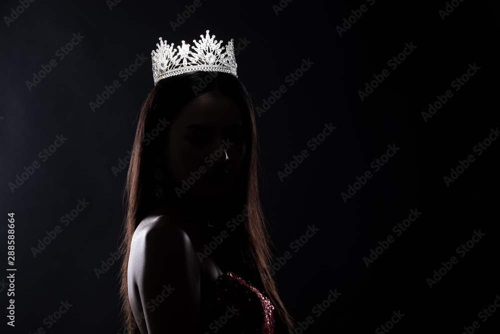 Fototapety, obrazy: Portrait of Miss Pageant Beauty Contest in sequin Evening Ball Gown long dress with sparkle light Diamond Crown, silhouette low key exposure with curtain, studio lighting dark background dramatic