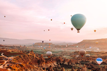 Colorful hot air balloons flying over the valley at Cappadocia sunrise time popular travel destination in Turkey