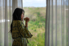 Lifestyle Portrait Of Young Beautiful Happy And Relaxed Asian Korean Woman In Stylish Bathrobe By Luxury Hotel Room Window Having Morning Coffee Enjoying The Tropical View