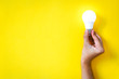 Leinwandbild Motiv man's hand holding LED light bulb over yellow  color background with copy space, flat lay, concept of ideas