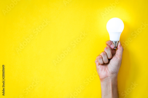 man's hand holding LED light bulb over yellow  color background with copy space, Wallpaper Mural