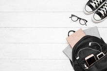 An Open Black Backpack With Books, A Mobile Phone, A Player With Headphones, Glasses, Gym Shoes On A White Wooden Background. Back To School. Student. Clean Space. Top View. Flat Lay