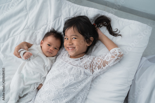 Fototapeta asian daughter kid with infant sibling playing on bed wearing white together obraz