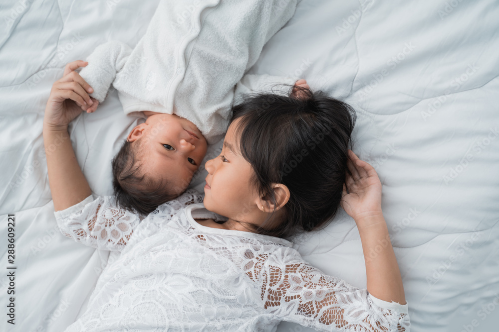 Fototapety, obrazy: top view of infant baby and girl sibling enjoying together on bed