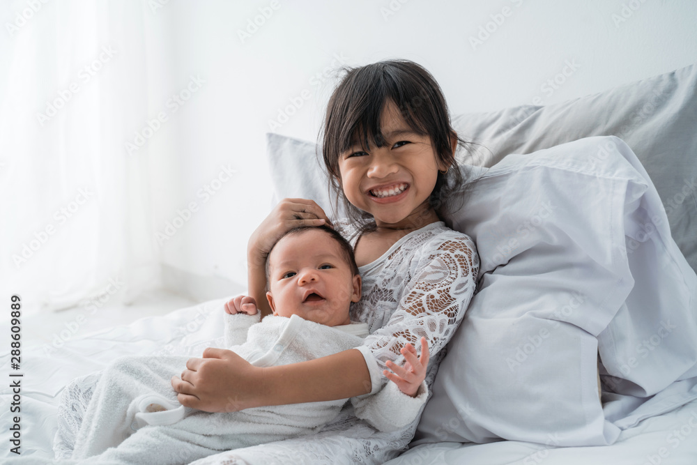 Fototapety, obrazy: smiling happy girl sibling infant lying on bed play together