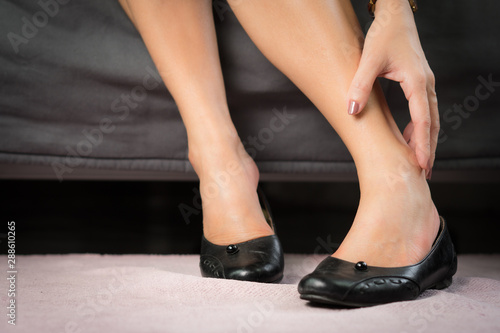 Cuadros en Lienzo  Closeup of a working woman hand taking off her too tight and narrow shoes after suffering for a long day pain and sore - Medical condition called bunions, Hallux valgus, Woman's Health - feet problem