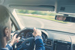 Selective focus of elderly man hands on steering wheel driving a car on the speed highway. View from above