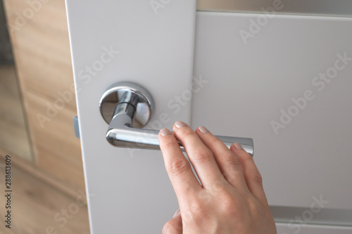 Obraz Female hand on metal door handle. Modern interior detail - fototapety do salonu