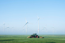 Farmer Mows Grass Near Wind Turbine Farm In Oastfriesland On Misty Summer Morning