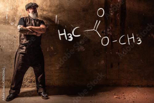 Fotografija  Bearded old man presenting handdrawn chemical formula of methyl acetate