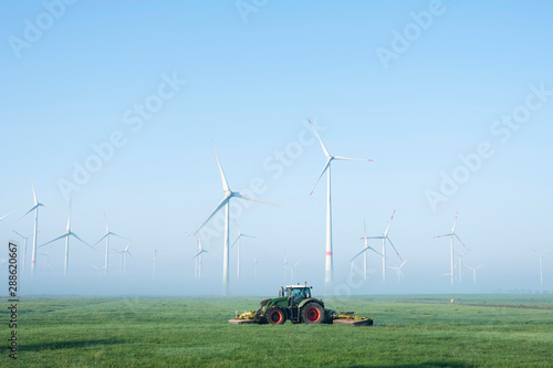 Fotografie, Obraz  farmer mows grass near wind turbine farm in oastfriesland on misty summer mornin