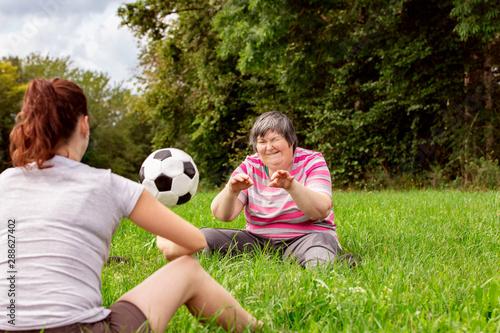 Papel de parede Zwei geistig behinderte Frauen werfen sich einen Ball zu, Übungen für Koordinati