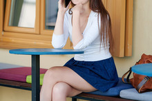 Stylish Beautiful Woman Sitting In City Cafe And Talking On A Smartphone In Blue Skirt With Crossed Legs. Unrecognizable Female In Short Skirt Sitting On Bench Between Tables At Cafe Terrace