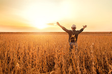 Rear View Of Senior Farmer Standing With His Outstretched In Soybean Field Examining Crop At Sunset.