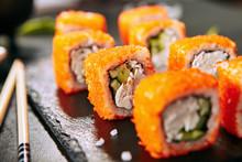 Macro Shot Of California Maki Sushi Rolls With Rice, Cream Cheese, Imitation Crab Meat, Cucumber, Orange Flying Fish Caviar And Nori. Fresh Crab Roll On Black Stone Background Closeup