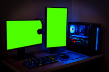 High-end PC Game Rig With Dual Mock Up Green Screen Or Chroma Key Monitor Stands. Modern Design Is Lit With Blue And Neon Light.