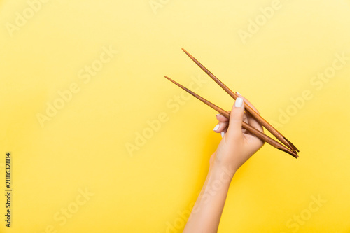 Female hand with chopsticks on yellow background Canvas Print