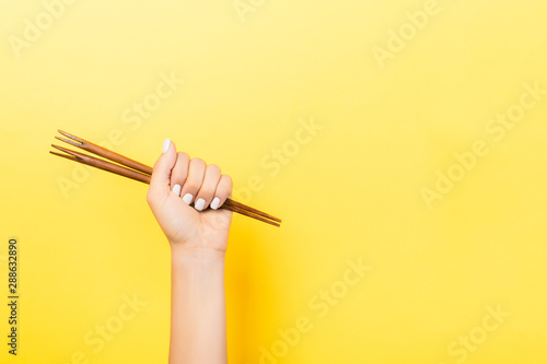 Cropped image of female hand holding chopsticks in fist on yellow background. Asian food concept with copy space