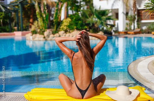 Fototapeta Sexy back of tanned slim model woman in black exotic bikini with hat enjoying in swimming pool