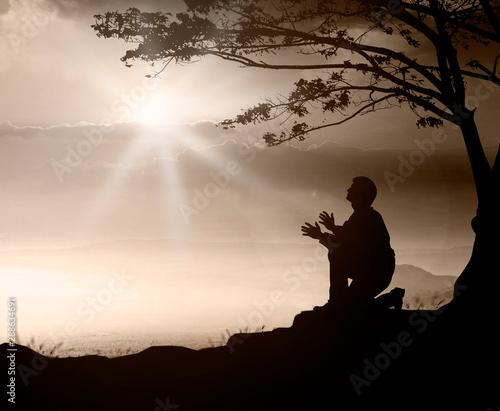 Obraz na plátně Pray concept: Humble man kneeling to praise and worship God on mountain sunset b